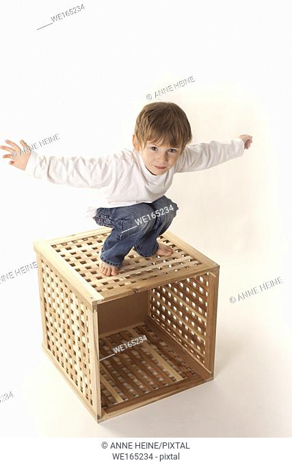 boy standing on box arms spread out, white