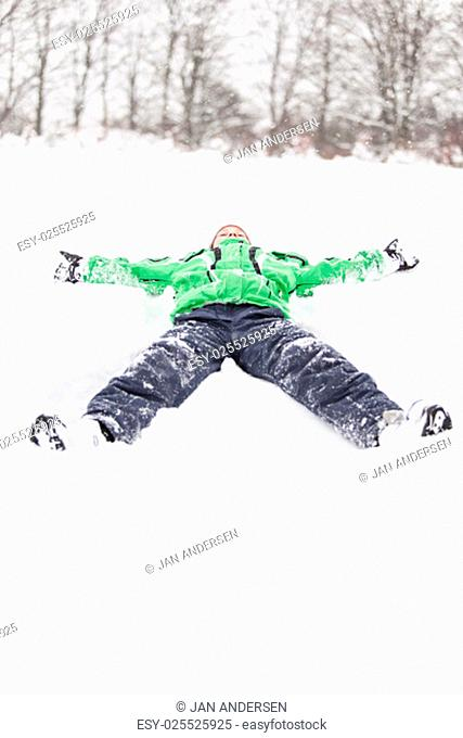 Young boy lying stretched out in the snow on his back with outstretched arms and legs as he enjoys the winter weather, with copyspace in the snow in the...