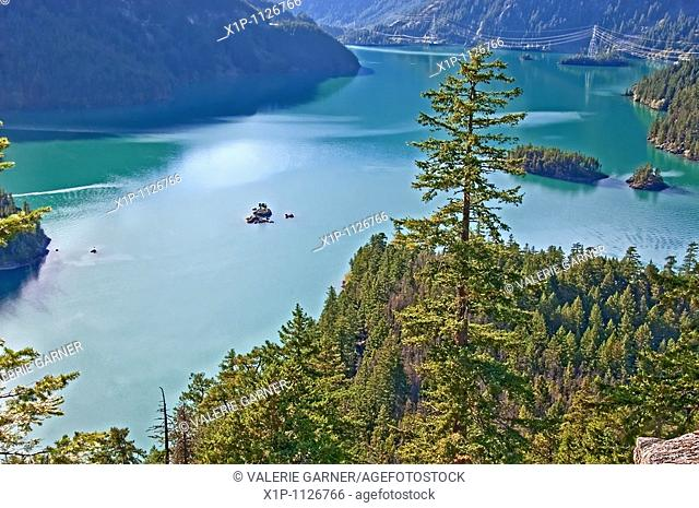 This landscape stock photo is a beautiful mountain lake with deep rich aquamarine colored water There's also several islands within the lake and evergreen and...