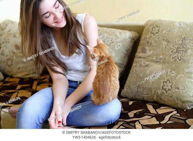 Teen girl sitting on sofa at home with kitty
