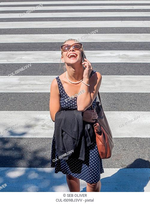 Young woman laughing on mobile phone on zebra crossing