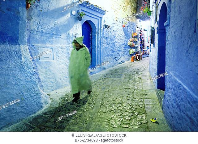 Man with a djellaba walking through the medina at dusk. Chaouen, Morocco