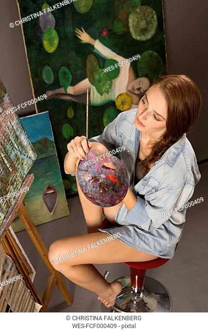 Young woman painting in studio
