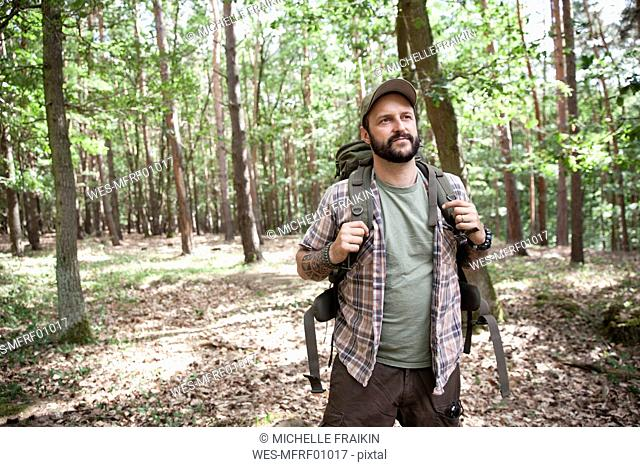 Serious man with backpack on a hiking trip in forest