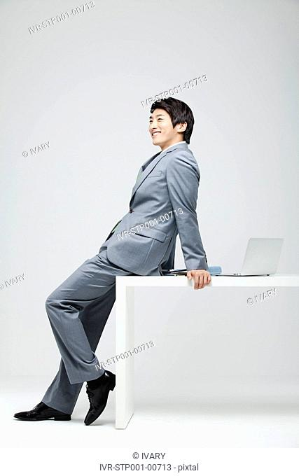 Portrait Of Smiling Asian Businessman Leaning On Desk, Laptop And File On Desk