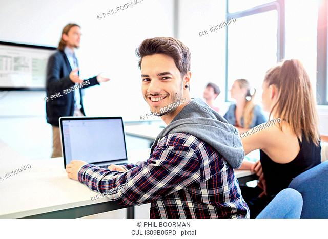 Portrait of young male student using laptop in higher education college classroom