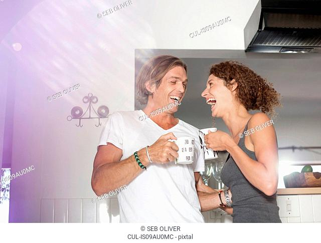 Couple in sleepwear, in kitchen, drinking coffee, laughing