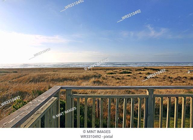 Balcony overlooking grassy field and beach