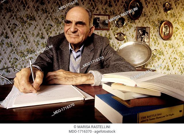 Attilio Bertolucci writing on a notebook, sitting at the desk. Emilian poet Attilio Bertolucci writes on a notebook, sitting at the writing desk full of books;...