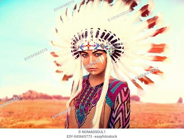 American Indian woman against mountain valley, Cherokee, Navajo. Headdress made of feathers of wild birds
