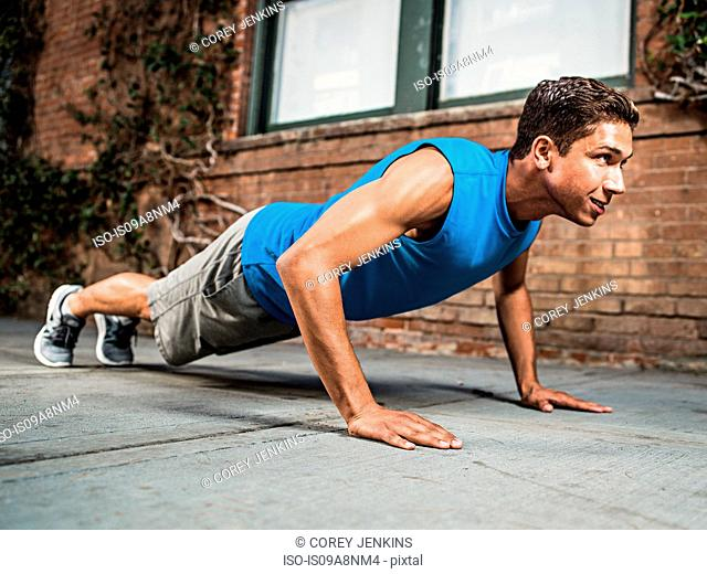Young man doing push-up on city street