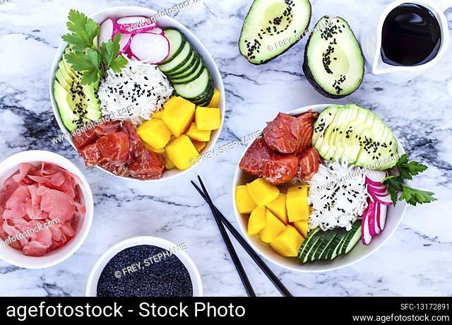 Hawaiian poke bowl with basmati rice, mango, raw salmon, avocado, radishes, cucumber, pickled ginger and black sesame