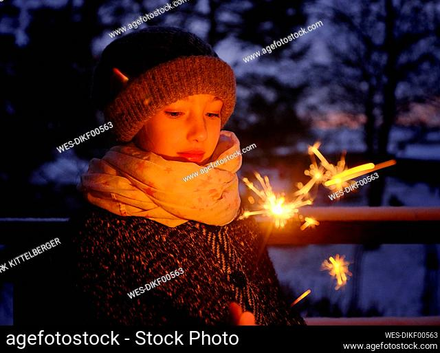 Girl in warm clothing with sparkler at dusk during winter