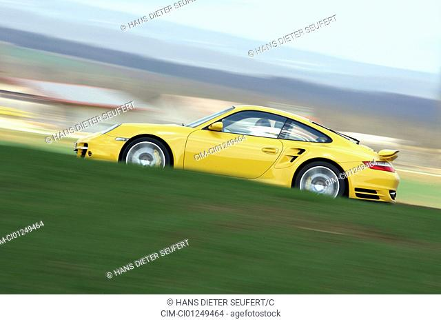 Porsche 911 turbo, model year 2006-, yellow, driving, side view, country road
