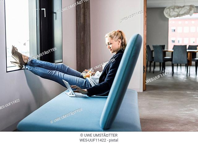 Businesswoman sitting on couch with feet up using tablet