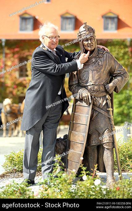 11 September 2021, Saxony-Anhalt, Ballenstedt: Eduard Prince of Anhalt stands by a sculpture of Albrecht the Bear, Count of Ballenstedt, in the castle courtyard