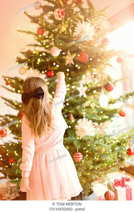 Girl in pink dress hanging ornaments on Christmas tree
