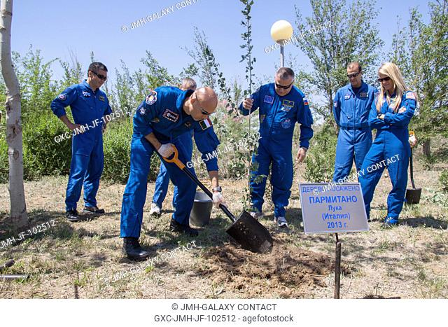 Behind the Cosmonaut Hotel crew quarters in Baikonur, Kazakhstan, Expedition 3637 Flight Engineer Luca Parmitano of the European Space Agency plants a tree in...
