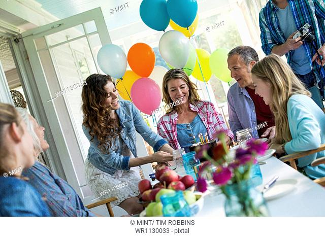 A birthday party in a farmhouse kitchen. A group of adults and children gathered around a chocolate cake