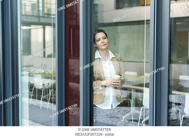 Female senior manager standing on window pane, coffee cup