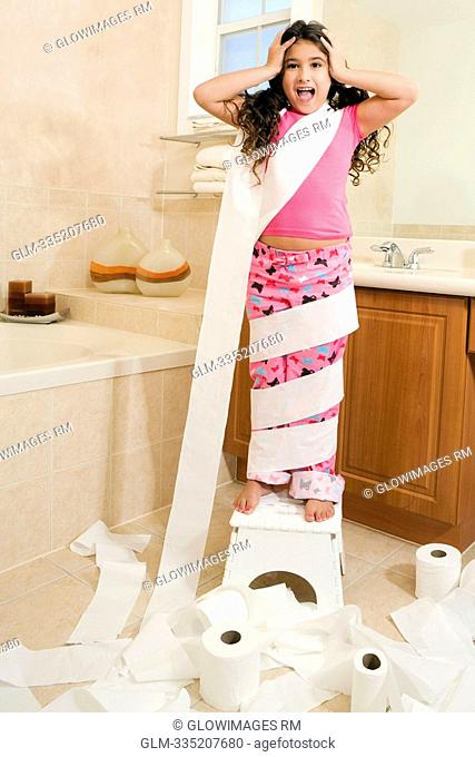 Girl wrapped in toilet papers in the bathroom