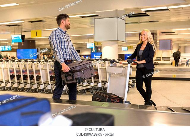 Mid adult couple collecting luggage from baggage claim area in airport and loading trolley