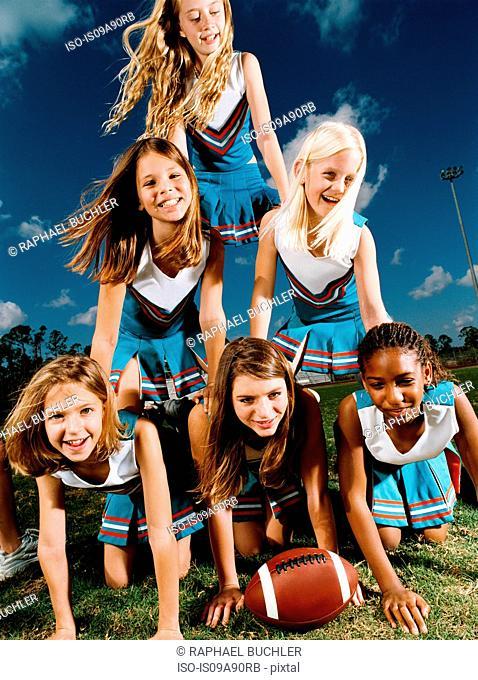 Cheerleaders kneeling on top of each other, portrait