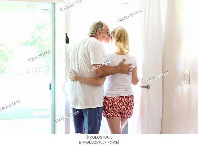 Caucasian couple kissing in patio doorway