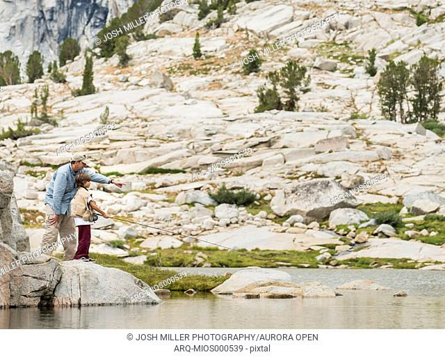 Father teaching son to flyfish at High Sierra lake, John Muir Wilderness Area, High Sierra