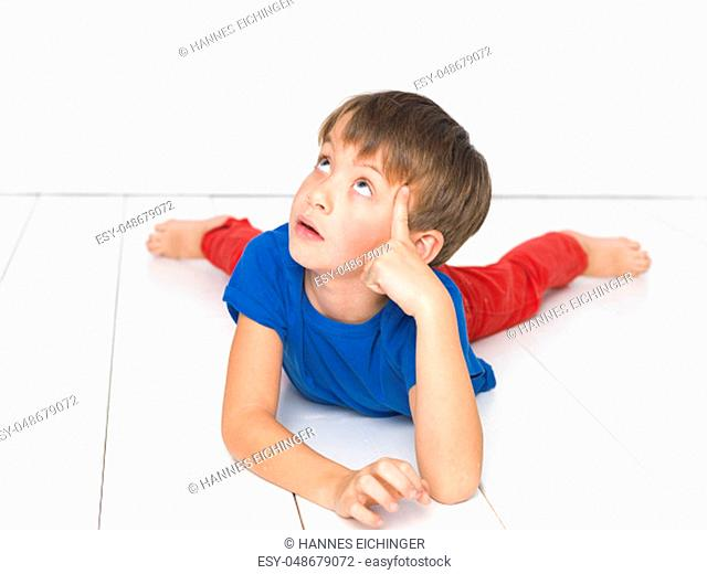 cool, six year old boy with red trousers and blue shirt on white floor
