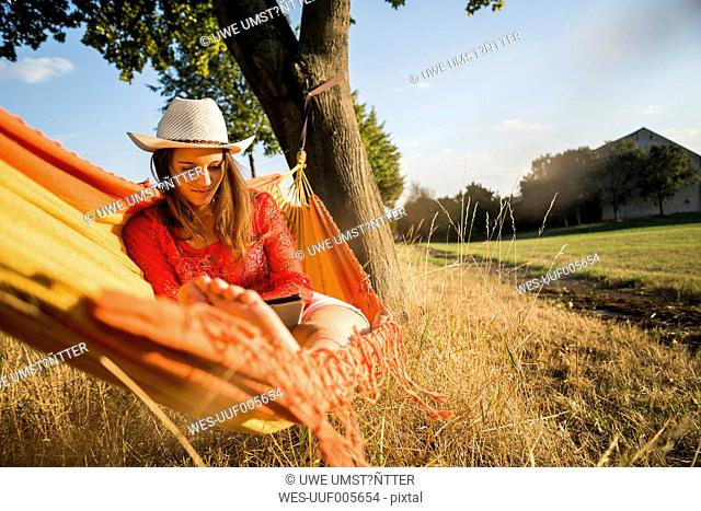 Woman wearing hat relaxing in a hammock with digital tablet