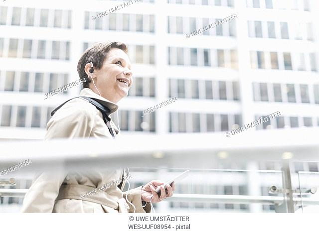 USA, New York City, smiling businesswoman on the go with cell phone and earphones