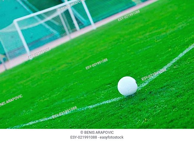 Soccer ball on grass at goal and stadium in background