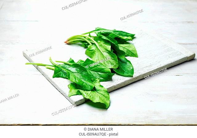 Whole leaf spinach on wooden chopping board