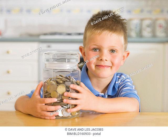 Caucasian boy holding coin jar in kitchen
