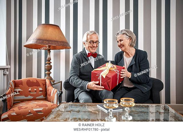 Happy senior couple sitting on couch with gift