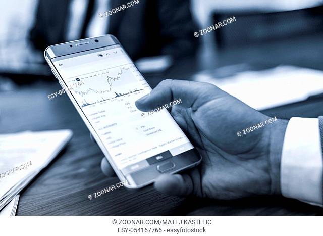 Close up of a businessman reviewing data on smart phone in corporate office. Focus on mobile device. Blue toned black and white image