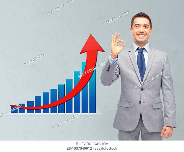 business, people, economics and financial success concept - happy smiling businessman in suit ok hand sign with growth chart over gray background