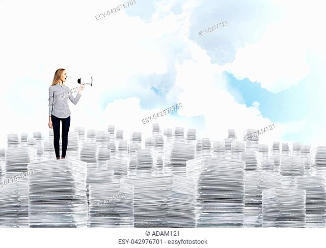 Woman in casual clothing standing on pile of documents with speaker in hand with cloudly skyscape on background. Mixed media