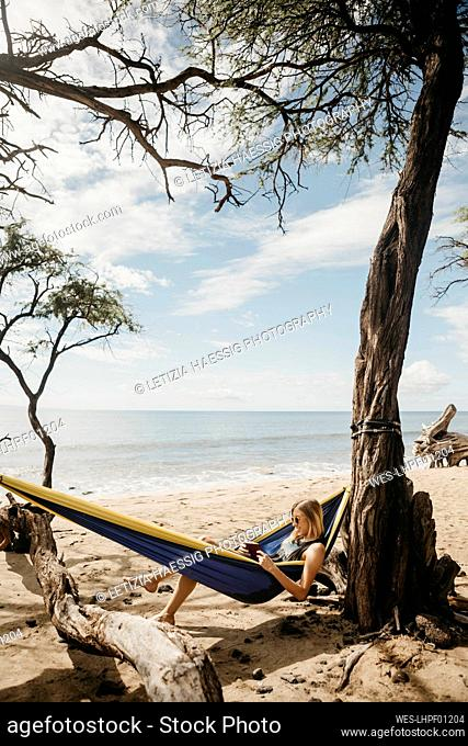 Young woman reading book while resting in hammock at beach, Maui, Hawaii, USA