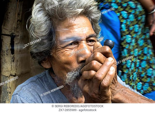 Local man smoking a joint on Shiva Day at Chitwan, Nepal. Marijuana or Cannabis is illegal in Nepal, but permitted as a religious ritual