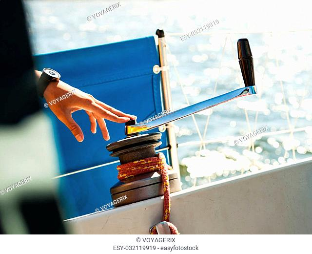 Male hand on winch capstan with rope on sailing boat. Yachting yacht in blue baltic sea sunny day summer vacation. Tourism luxury lifestyle