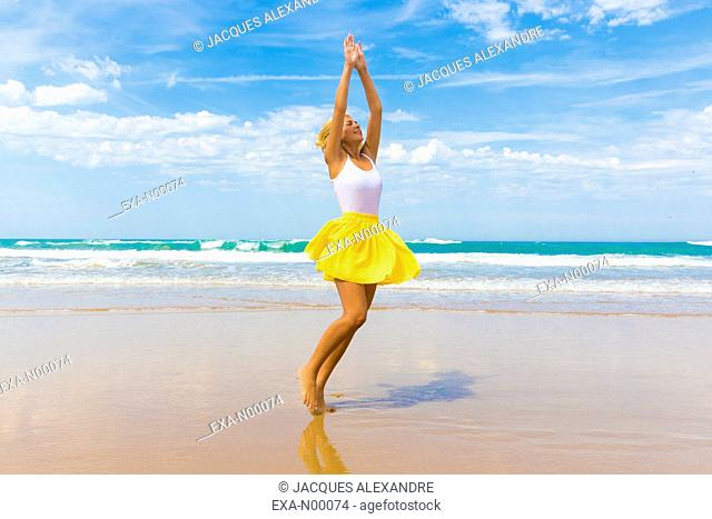 Happy girl with yellow skirt dancing on a beach in Biarritz, France