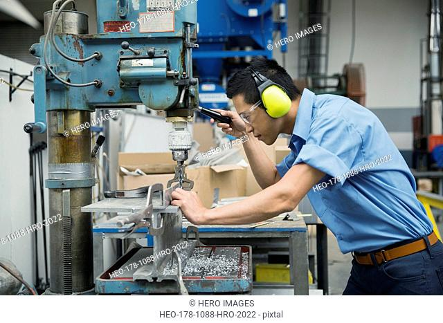 Worker operating drill machinery in manufacturing plant