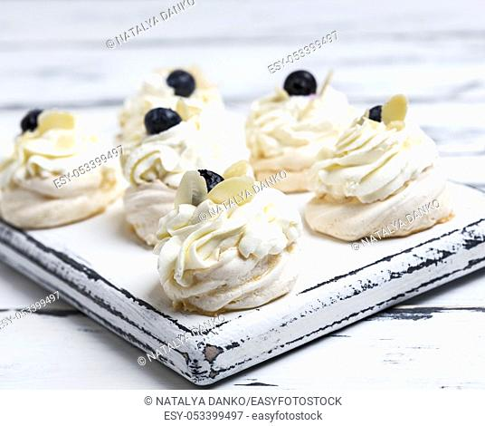 small baked round cake meringue with whipped cream on a white wooden board