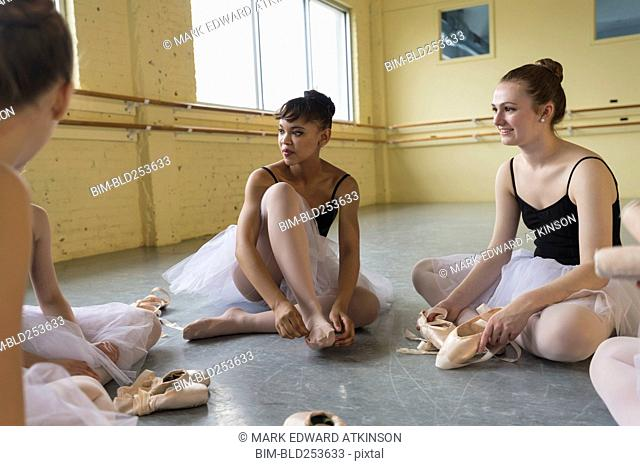 Girls sitting on floor and talking in ballet studio