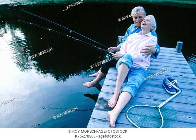 Senior couple fishing and laughing
