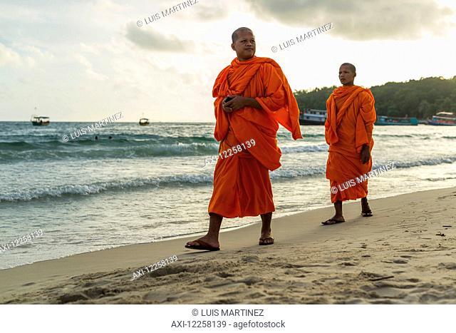 Monks walking on the sand of Serendipity Beach; Sihanoukville, Cambodia