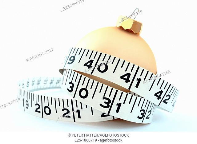 a christmas eating & excess concept featuring a tape measure around a gold coloured bauble