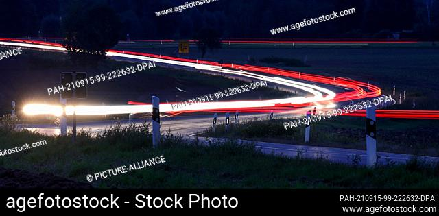 15 September 2021, Saxony, Leipzig: Cars drive in the early morning over a country road at the outskirts of Leipzig. (Shot with a long exposure time) Photo: Jan...